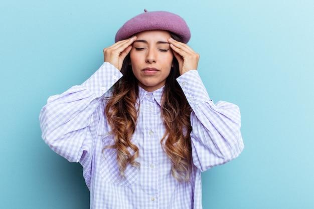Jeune femme mexicaine isolée sur fond bleu touchant les temples et ayant des maux de tête.