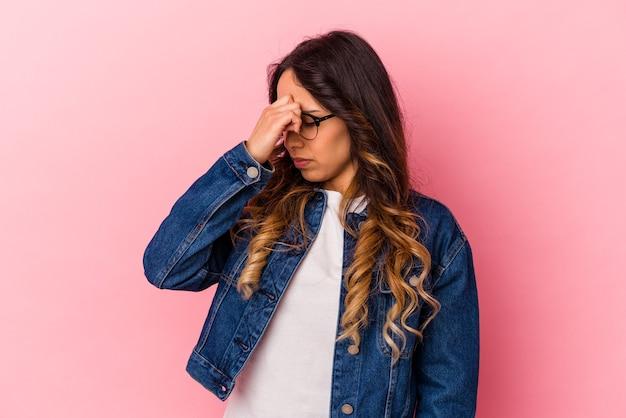 Jeune femme mexicaine isolée sur fond rose ayant un mal de tête, touchant le devant du visage.