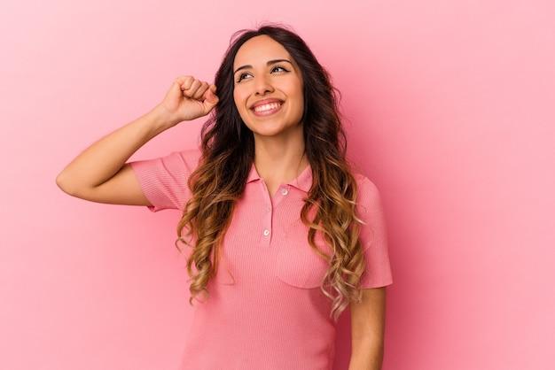Jeune femme mexicaine isolée sur fond rose célébrant une victoire, une passion et un enthousiasme, une expression heureuse.