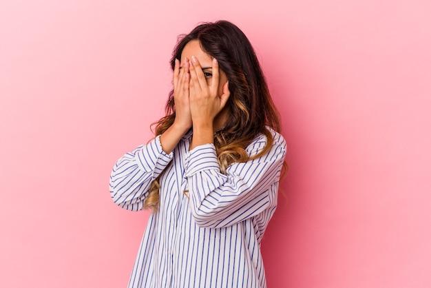 Jeune femme mexicaine isolée sur fond rose clignote à travers les doigts effrayés et nerveux.