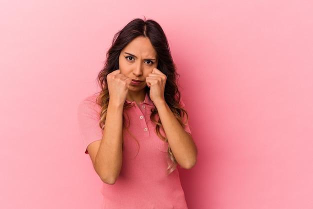 Jeune femme mexicaine isolée sur fond rose jetant un coup de poing, colère, combat à cause d'une dispute, boxe.