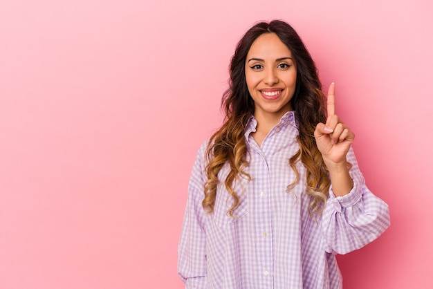Jeune femme mexicaine isolée sur fond rose montrant le numéro un avec le doigt.
