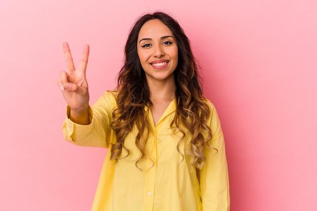 Jeune femme mexicaine isolée sur fond rose montrant le signe de la victoire et souriant largement.