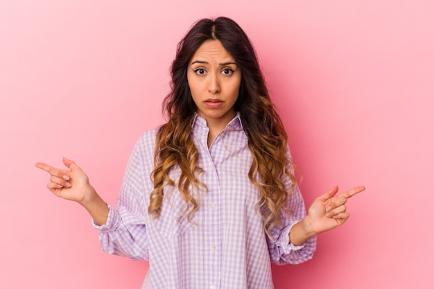 Jeune femme mexicaine isolée sur fond rose pointant vers différents espaces de copie, en choisissant l'un d'entre eux, montrant avec le doigt.