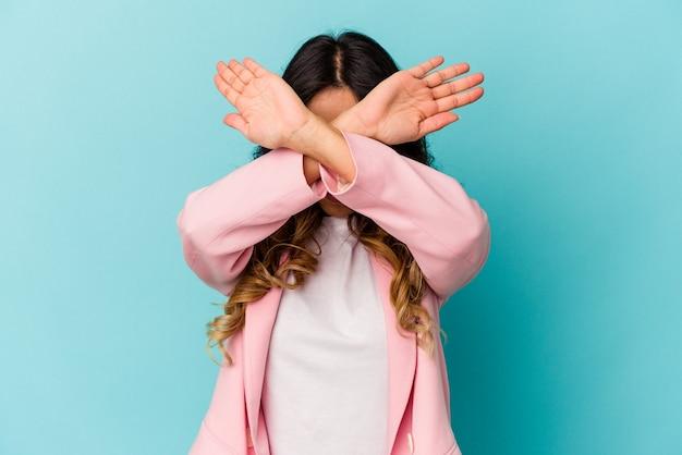 Jeune femme mexicaine isolée sur un mur bleu en gardant deux bras croisés, concept de déni.