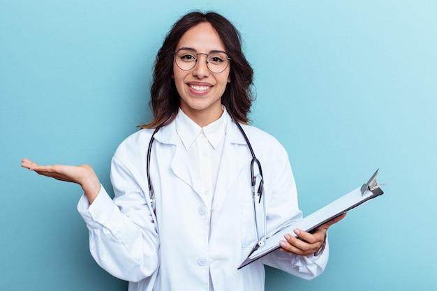 Jeune femme mexicaine médecin isolée sur fond bleu montrant un espace de copie sur une paume et tenant une autre main sur la taille.