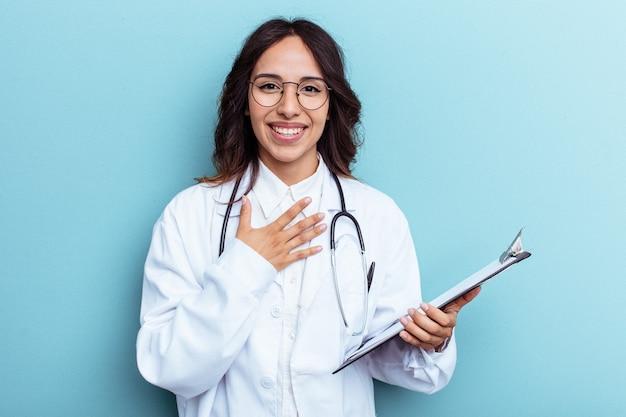 Jeune femme mexicaine médecin isolée sur fond bleu rit fort en gardant la main sur la poitrine.