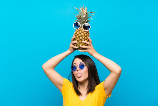 Jeune femme mexicaine sur un mur bleu isolé, tenant un ananas avec des lunettes de soleil