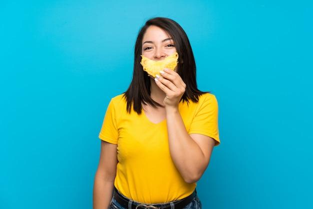Jeune femme mexicaine sur un mur bleu isolé