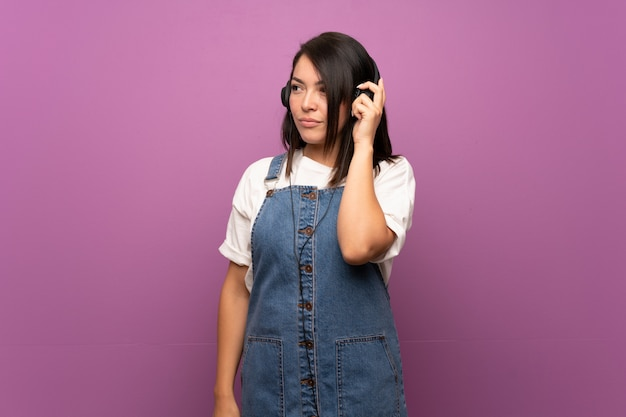 Jeune femme mexicaine sur mur isolé, écouter de la musique avec des écouteurs
