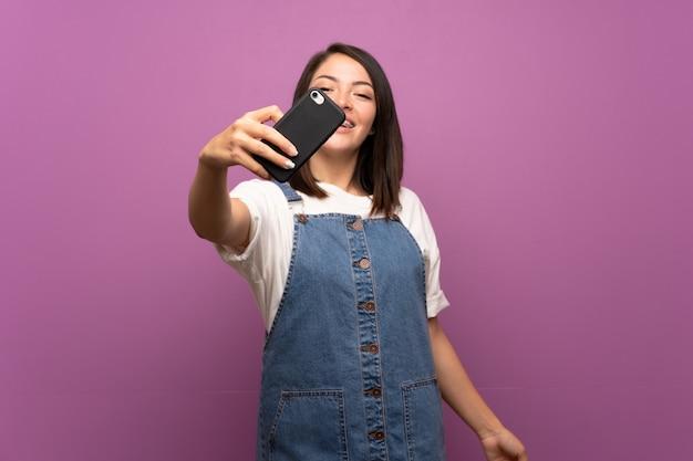 Jeune femme mexicaine sur mur isolé faisant selfie avec téléphone portable
