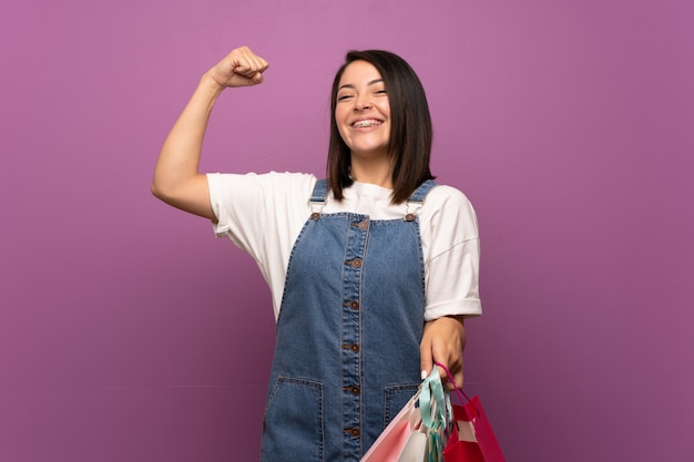 Jeune femme mexicaine sur mur isolé tenant beaucoup de sacs à provisions