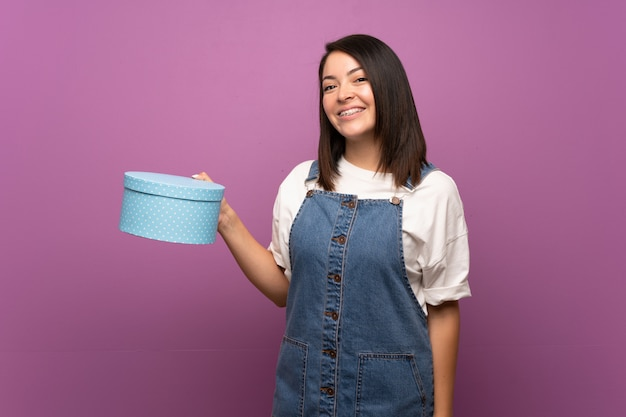 Jeune femme mexicaine sur mur isolé tenant une boîte-cadeau