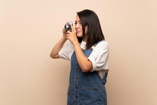 Jeune femme mexicaine sur mur isolé, tenant une caméra
