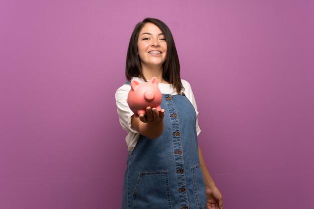 Jeune femme mexicaine sur mur isolé tenant une grande tirelire