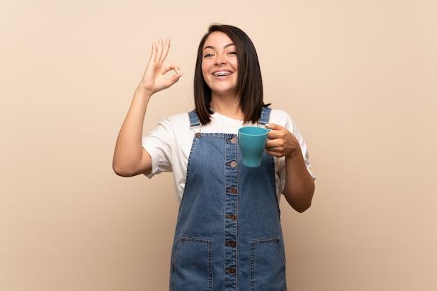 Jeune femme mexicaine sur mur isolé, tenant une tasse de café