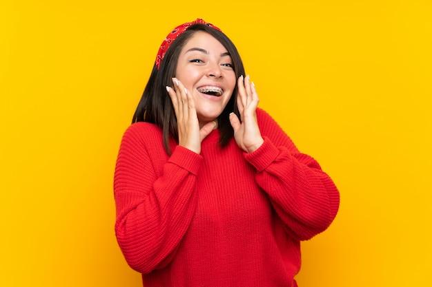 Jeune femme mexicaine avec un pull rouge sur un mur jaune avec une expression faciale surprise