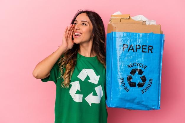 Jeune femme mexicaine recyclage du carton isolé sur fond rose criant et tenant la paume près de la bouche ouverte.