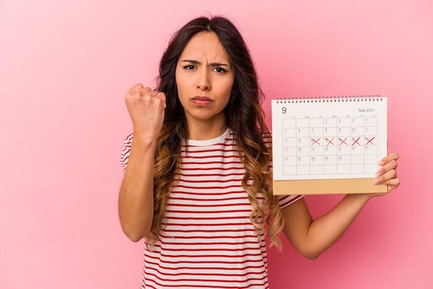 Jeune femme mexicaine tenant un calendrier isolé sur fond rose montrant le poing à la caméra, expression faciale agressive.