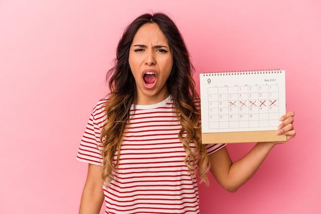Jeune femme mexicaine tenant un calendrier isolé sur un mur rose criant très en colère et agressif.