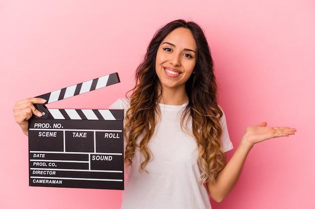 Jeune femme mexicaine tenant clap isolé sur fond rose montrant un espace de copie sur une paume et tenant une autre main sur la taille.