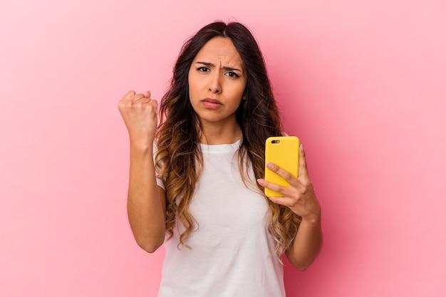 Jeune femme mexicaine tenant un téléphone portable isolé sur fond rose montrant le poing à la caméra, expression faciale agressive.