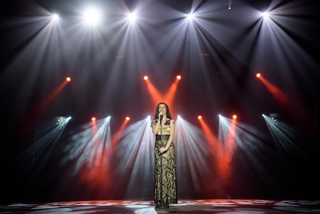 Jeune femme avec microphone à la main sur événement de divertissement.