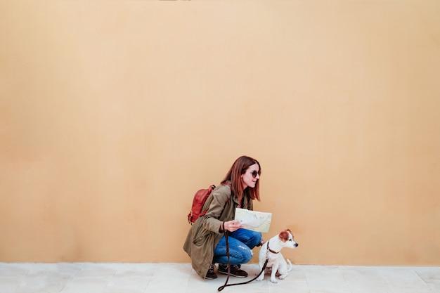 Jeune femme et mignon chien jack russell dans une ville à la recherche d'une carte. concept de voyage