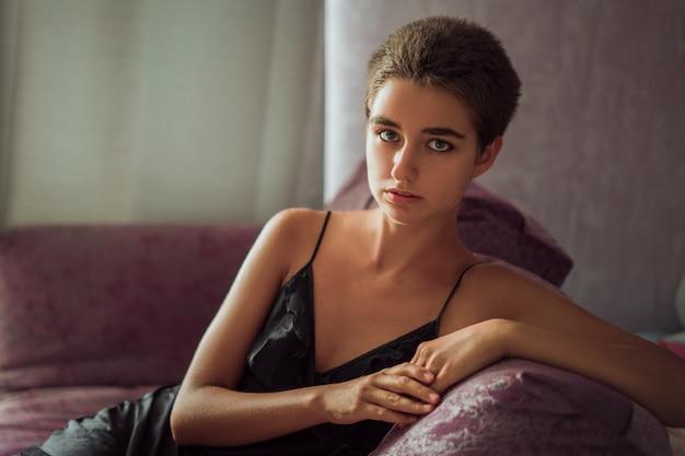 Jeune femme mignonne assise sur une chaise triste, cheveux courts