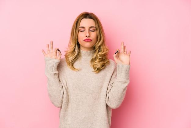 Jeune femme mignonne blonde portant un pull isolé se détend après une dure journée de travail, elle effectue du yoga.
