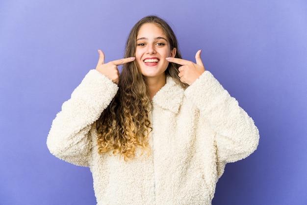 Jeune femme mignonne caucasienne sourit, pointant du doigt la bouche.