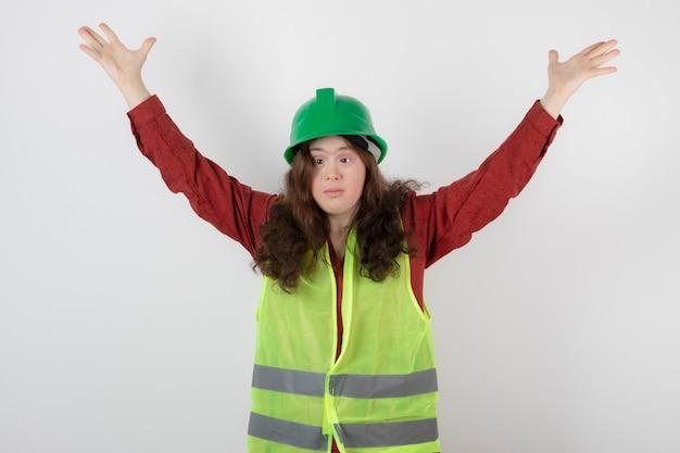Jeune femme mignonne debout en gilet et posant les mains en levant.