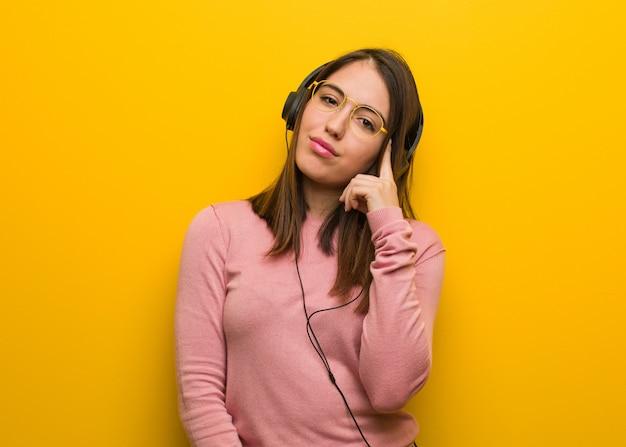 Jeune femme mignonne écoutant de la musique en pensant à une idée