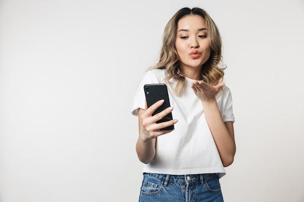 Jeune Femme Mignonne émotionnelle Posant Isolée Sur Un Mur Blanc Parlant Par Téléphone Portable Soufflant Des Baisers Photo Premium