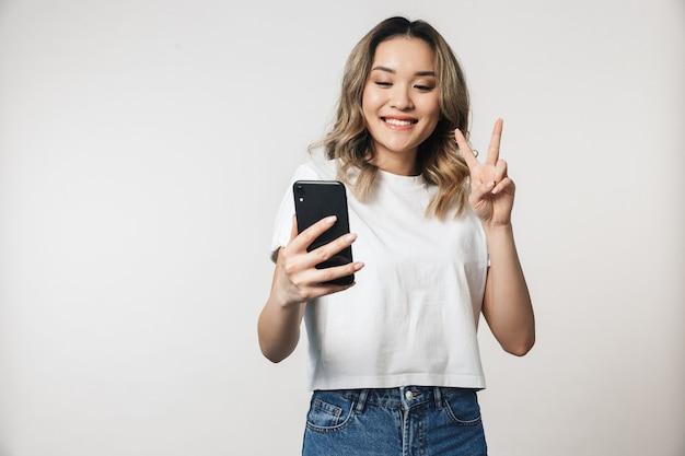 Jeune femme mignonne émotionnelle posant isolée sur un mur blanc parlant par téléphone portable