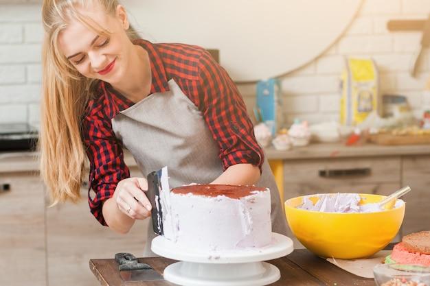 Jeune femme mignonne faisant un gâteau biscuit avec de la crème blanche sur une table de cuisine en bois.