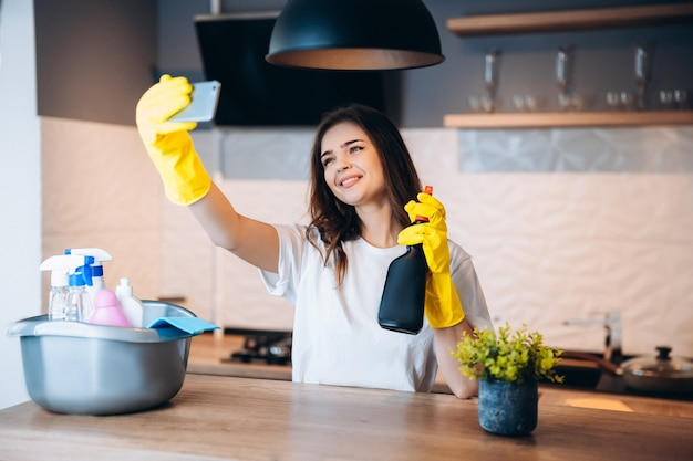 Jeune femme mignonne heureuse en gants jaunes prend selfie tout en nettoyant sa cuisine à la maison avec des détergents
