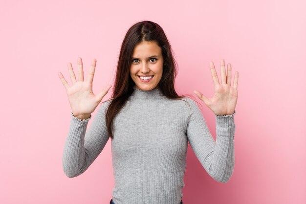 Jeune femme mignonne montrant le numéro dix avec les mains.