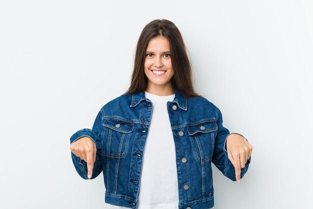 Jeune femme mignonne pointe vers le bas avec les doigts, sentiment positif.