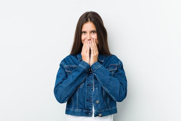 Jeune femme mignonne, riant de quelque chose, couvrant la bouche avec les mains.