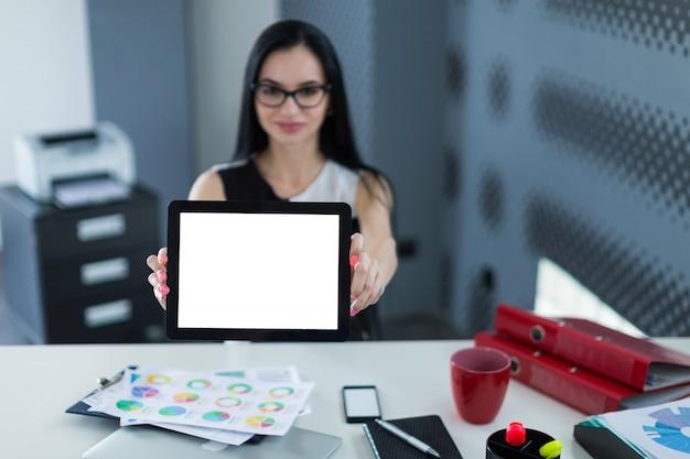 Jeune femme mignonne en robe noire et lunettes s'asseoir à la table et montrer la tablette vide