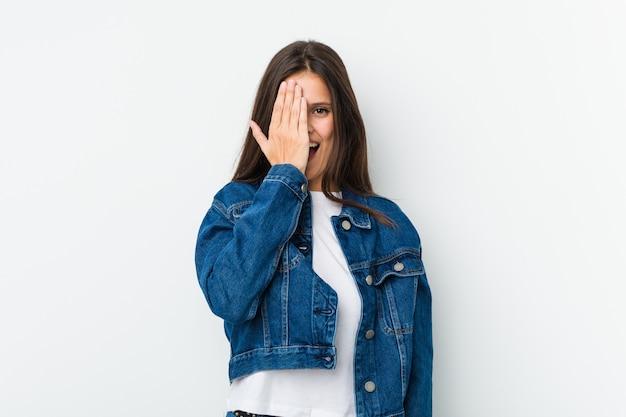 Jeune femme mignonne s'amuser couvrant la moitié du visage avec la paume.