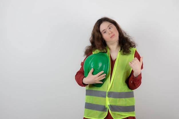 Jeune femme mignonne avec le syndrome de down debout dans un gilet et tenant des casques de protection.