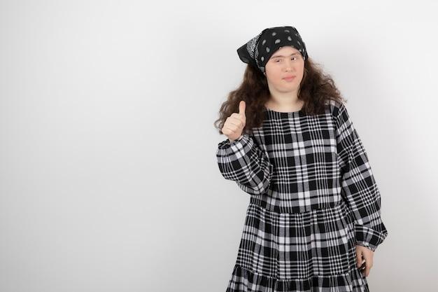 Jeune femme mignonne avec le syndrome de down debout et montrant un pouce vers le haut.
