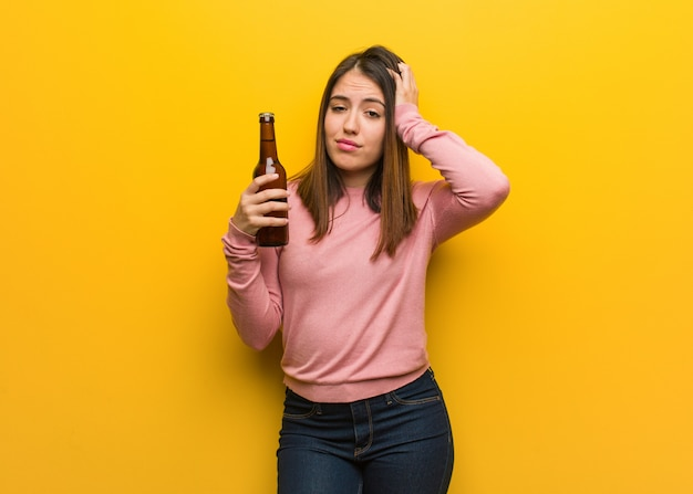 Jeune femme mignonne tenant une bière inquiète et débordée