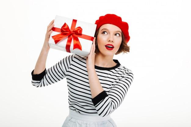 Jeune femme mignonne tenant la boîte surprise cadeau.