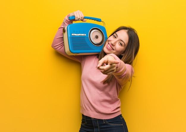 Jeune femme mignonne tenant une radio vintage joyeuse et souriante pointant vers l'avant