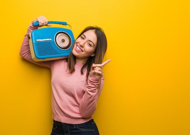 Jeune femme mignonne tenant une radio vintage pointant sur le côté avec le doigt