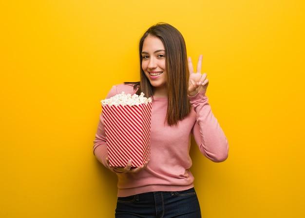 Jeune femme mignonne tenant un seau de pop-corn amusant et heureux de faire un geste de victoire