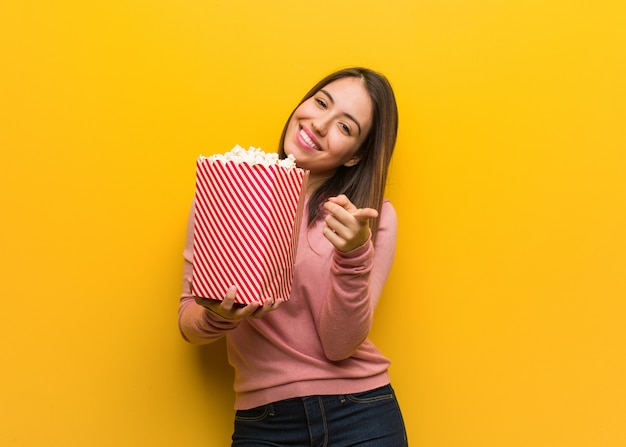 Jeune femme mignonne tenant un seau de pop-corn gai et souriant pointant vers l'avant